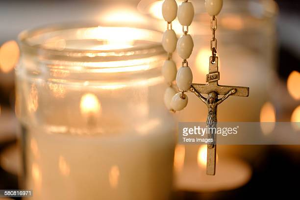USA, New Jersey, Burning candles with rosary in foreground