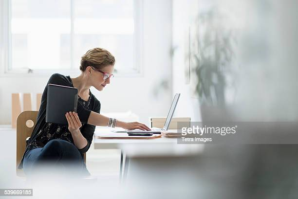 USA, New Jersey, Businesswoman using laptop in office