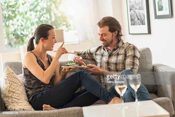 USA, New Jersey, Cheerful couple eating on sofa
