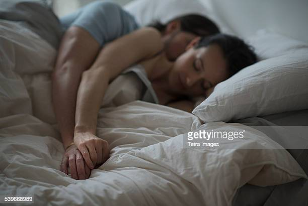 USA, New Jersey, Couple sleeping together in bed at night
