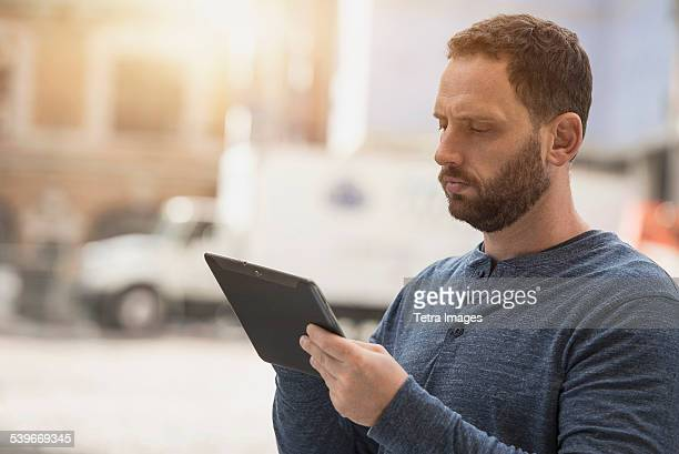 USA, New Jersey, Delivery man using digital tablet