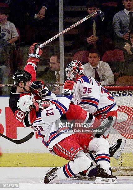New Jersey Devils' Bobby Holik takes down New York Rangers' Mathieu Schneider in front of the Rangers' goal for a holding penalty late in the third...