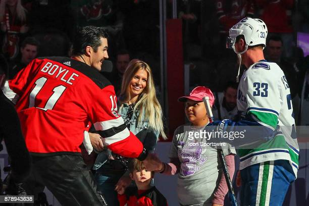 New Jersey Devils center Brian Boyle and Vancouver Canucks center Henrik Sedin shake hands with a young cancer patient prior to the National Hockey...