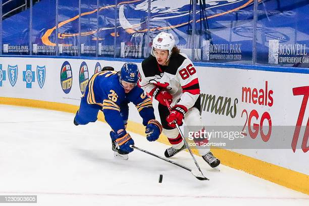 New Jersey Devils center Jack Hughes skates with puck as Buffalo Sabres defenseman Rasmus Dahlin dives to knock puck away during the New Jersey...