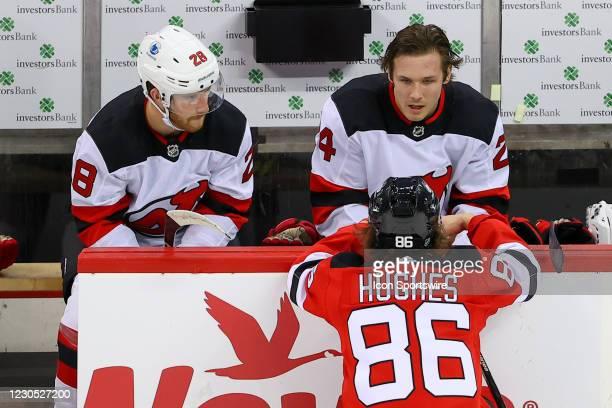 New Jersey Devils center Jack Hughes talks with New Jersey Devils defenseman Damon Severson and New Jersey Devils defenseman Ty Smith on the bench...
