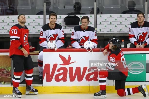 New Jersey Devils center Jack Hughes talks with New Jersey Devils defenseman Dmitry Kulikov , New Jersey Devils defenseman Damon Severson and New...