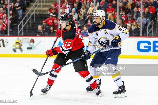 New Jersey Devils center Nico Hischier battles Buffalo Sabres defenseman Zach Bogosian during the third period of the National Hockey League Game...
