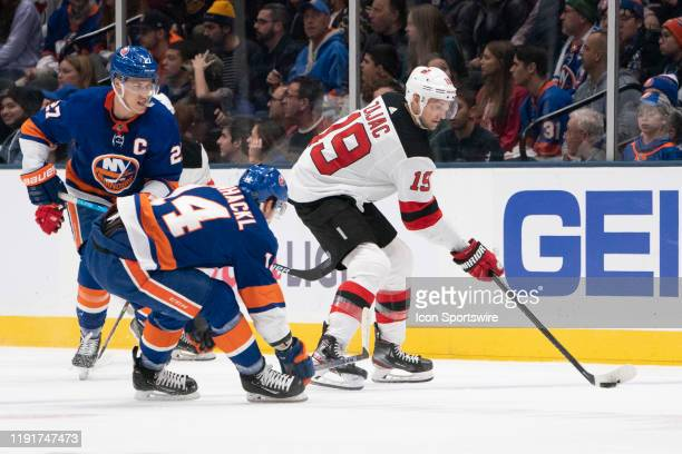 New Jersey Devils Center Travis Zajac controls the puck with New York Islanders Right Wing Tom Kuhnhackl defending and during the first period of the...
