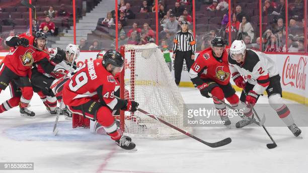 New Jersey Devils Defenceman John Moore stickhandles the puck behind the Senators goal as ott49 and Ottawa Senators Left Wing Ryan Dzingel defend...