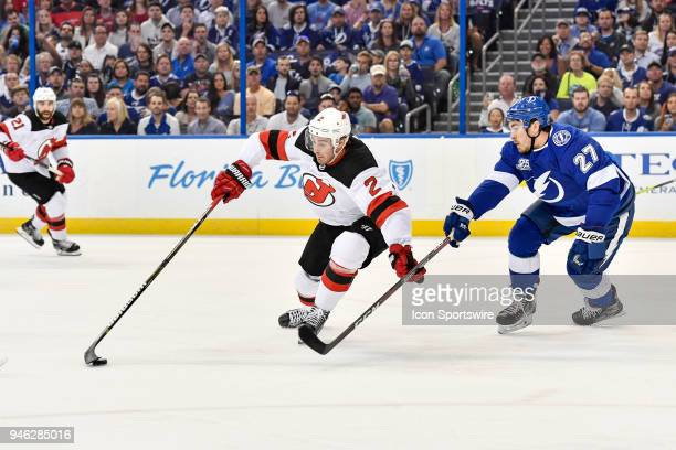 New Jersey Devils defender John Moore protects the puck from Tampa Bay Lightning defender Ryan McDonagh during the first period of an NHL Stanley Cup...