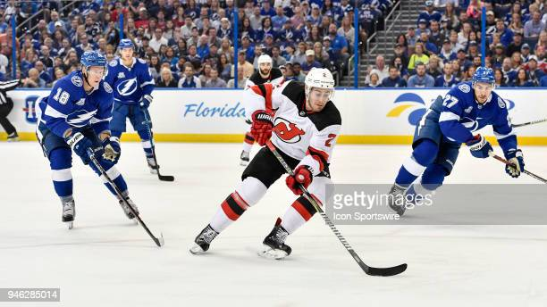 New Jersey Devils defender John Moore splits Tampa Bay Lightning left wing Ondrej Palat and Tampa Bay Lightning defender Ryan McDonagh to take a...