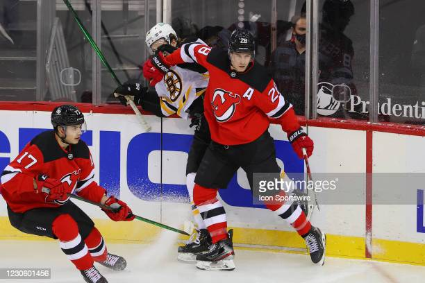 New Jersey Devils defenseman Damon Severson hits Boston Bruins right wing Chris Wagner during the National Hockey League game between the New Jersey...