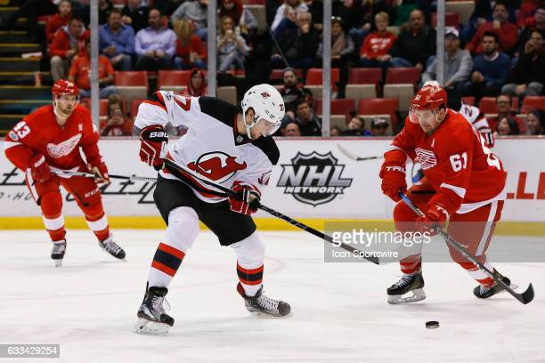 New Jersey Devils forward Pavel Zacha of the Czech Republic and Detroit Red Wings defenseman Xavier Ouellet of France battle for control of the puck...