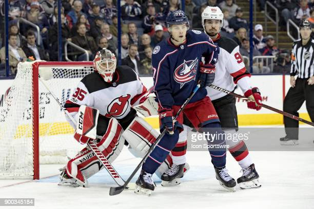 New Jersey Devils goalie Cory Schneider looks around Columbus Blue Jackets right wing Josh Anderson during a game between the Columbus Blue Jackets...