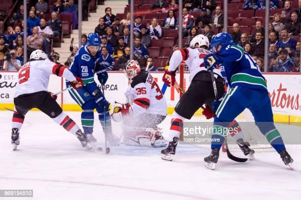 New Jersey Devils Goalie Cory Schneider makes a save on Vancouver Canucks Center Brandon Sutter as New Jersey Devils Left Wing Taylor Hall defends...