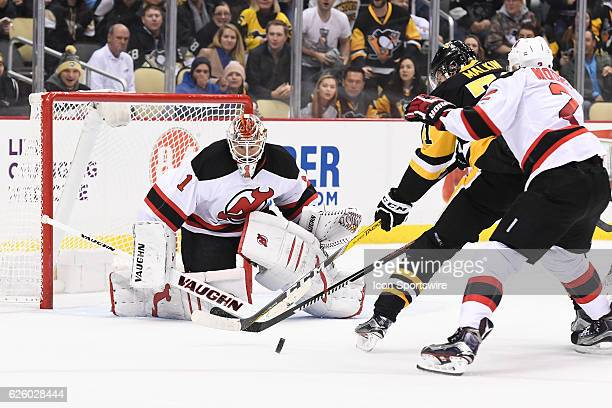 New Jersey Devils Goalie Keith Kinkaid makes a save on Pittsburgh Penguins Center Evgeni Malkin as New Jersey Devils Defenceman John Moore defends...