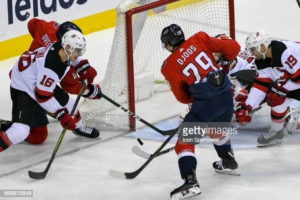 New Jersey Devils goaltender Cory Schneider and defenseman Steven Santini make a third period save on a shot by Washington Capitals left wing Alex...