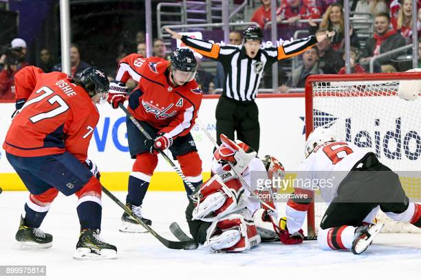 New Jersey Devils goaltender Cory Schneider has a shot deflect off of his pads in the second period as defenseman Andy Greene moves in to make the...