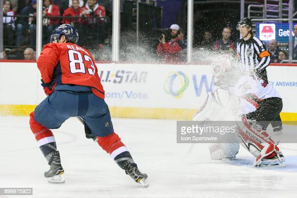 New Jersey Devils goaltender Cory Schneider is covered with ice off the skates of Washington Capitals center Jay Beagle in the first period on...