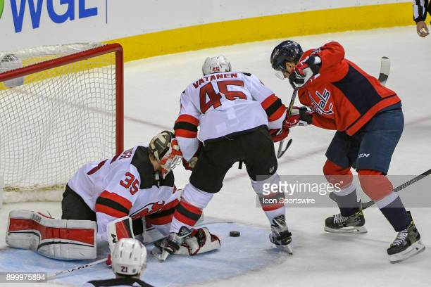 New Jersey Devils goaltender Cory Schneider makes a save in the third period against Washington Capitals right wing Alex Chiasson on December 30 at...
