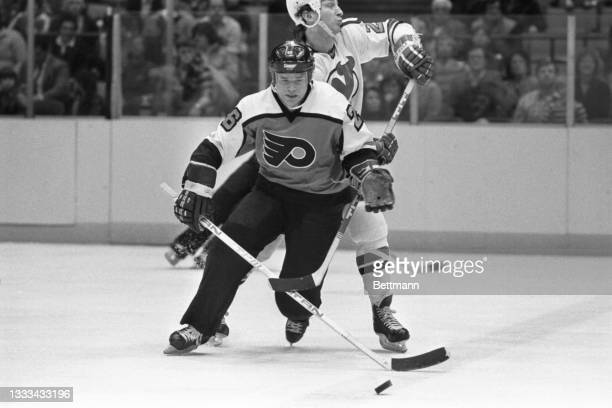 New Jersey Devils' Hector Marini uses his stick to prevent Philadelphia Flyers' Brian Propp from getting to the puck during the first period of their...
