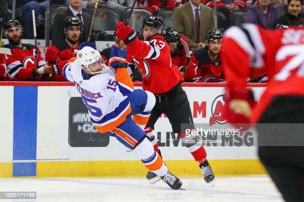 New Jersey Devils left wing Brett Seney hits New York Islanders right wing Cal Clutterbuck during the first period of the National Hockey League game...