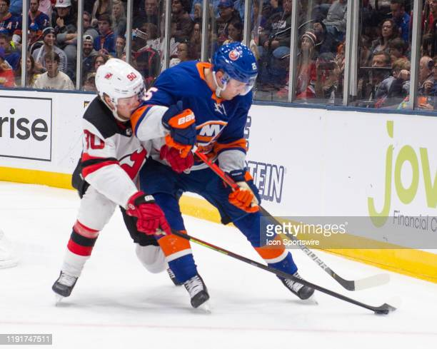 New Jersey Devils Left Wing Jesper Boqvist and New York Islanders Defenseman Devon Toews battle for the puck during the third period of the National...