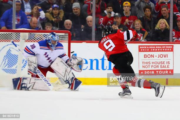 New Jersey Devils left wing Taylor Hall shoots and scores on a penalty shot against New York Rangers goaltender Henrik Lundqvist during the second...