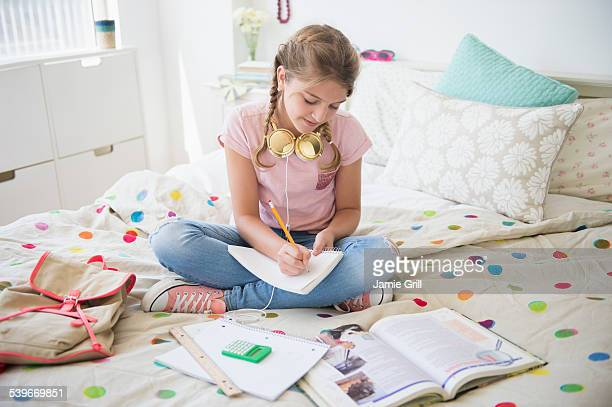 USA, New Jersey, Girl (12-13) sitting on bed doing homework