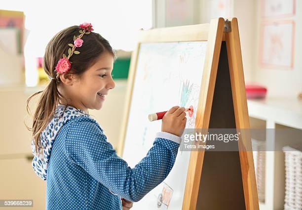 USA, New Jersey, Girl (6-7) writing on board in classroom