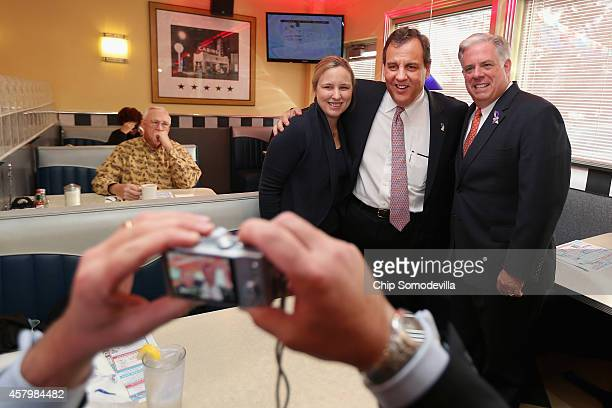 New Jersey Gov. Chris Christie and Maryland Republican gubernatorial candidate Larry Hogan pose for photographs with customers during a campaign stop...