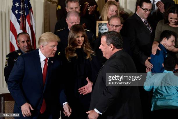 New Jersey Governor Chris Christie gets up to shake US President Donald Trump's hand during an event about the opioid problem in the East Room of the...