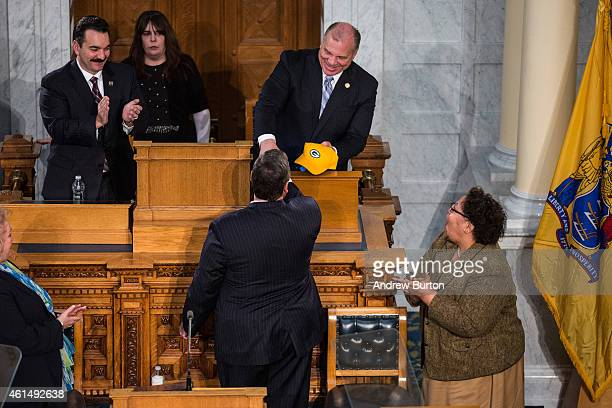 New Jersey Governor Chris Christie is given a Green Bay Packers hat by New Jersey Senate President Stephen Sweeney after the annual State of the...
