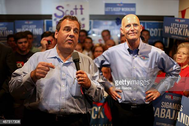 New Jersey Governor Chris Christie stands with Florida Governor Rick Scott as they make a campaign stop at a Vero Beach Field Office on October 16,...