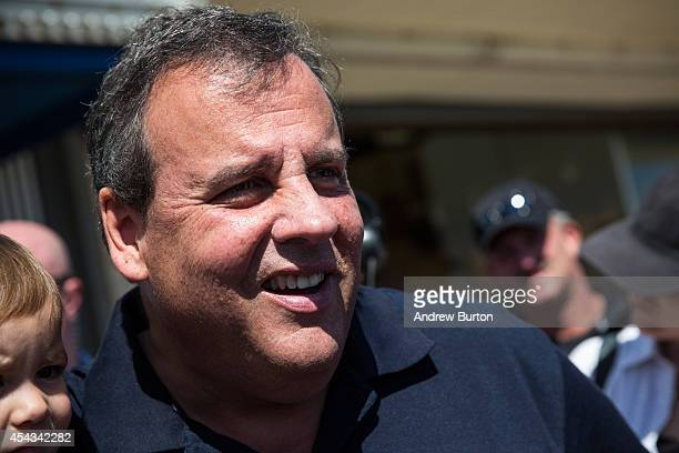 New Jersey Governor Chris Christie takes a photo with a family while touring the boardwalk on August 29 2014 in Seaside Heights New Jersey Christie...