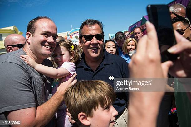 New Jersey Governor Chris Christie takes a photo with a family while touring the boardwalk on August 29 2014 in Point Pleasant New Jersey Christie...