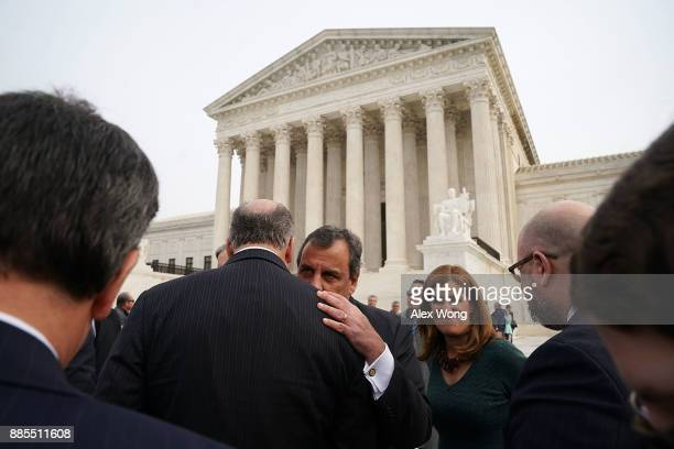 New Jersey Governor Chris Christie talks to an unidentified man as his wife Mary Pat Christie looks on in front of the US Supreme Court December 4...