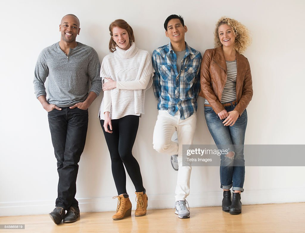 USA, New Jersey, Group of friends standing in front of white wall : Stock Photo