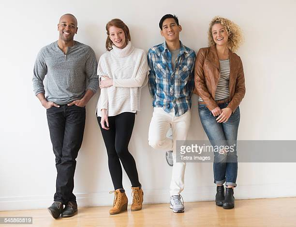 USA, New Jersey, Group of friends standing in front of white wall