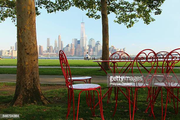 USA, New Jersey, Hoboken, Lower Manhattan skyline as seen from Pier A Park with public red metal table and chairs