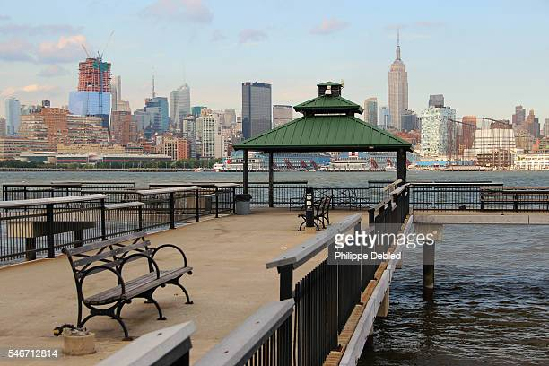 usa, new jersey, hoboken, midtown manhattan skyline and empire state building with gazebo and benches on a pier walkway of frank sinatra park - hoboken stock pictures, royalty-free photos & images