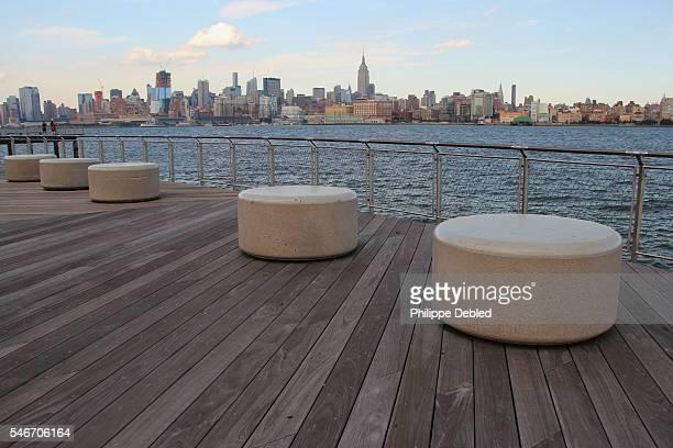 USA, New Jersey, Hoboken, Public stone round seats with Midtown Manhattan skyline