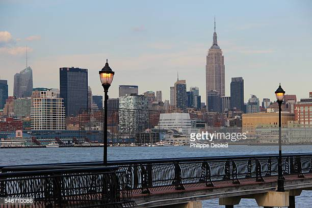 USA, New Jersey, Hoboken, Skyline of Midtown Manhattan and Empire State Building with a pier walkway of Frank Sinatra Park on the Hudson river in the foreground