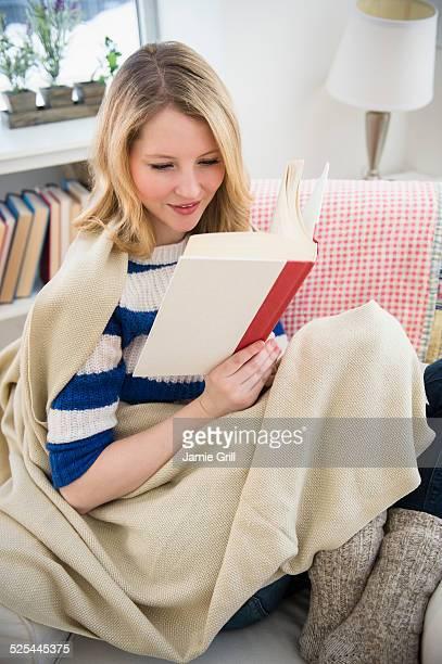 USA, New Jersey, Jersey City, Blond woman reading on sofa