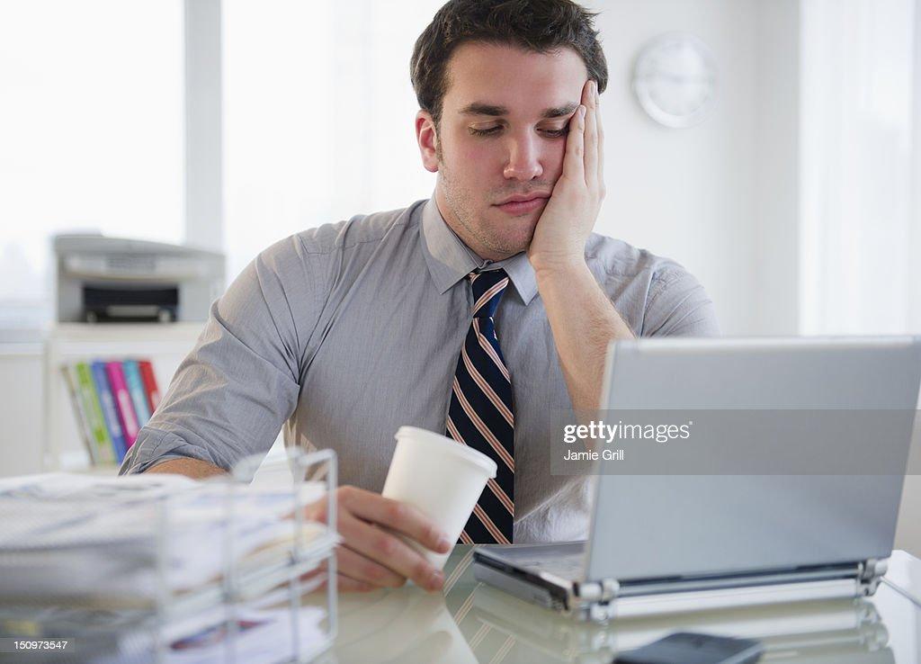 USA, New Jersey, Jersey City, Bored business man working on laptop : Stock Photo