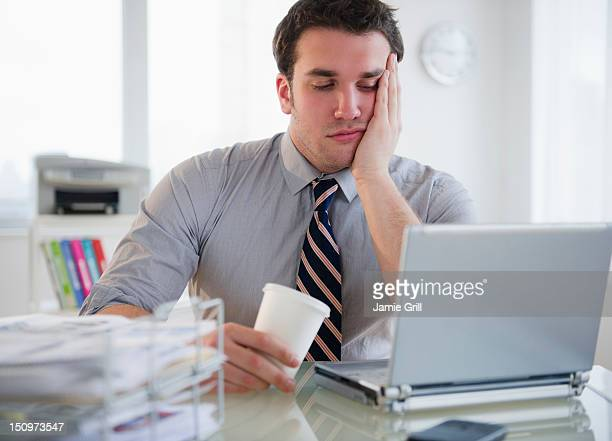 USA, New Jersey, Jersey City, Bored business man working on laptop