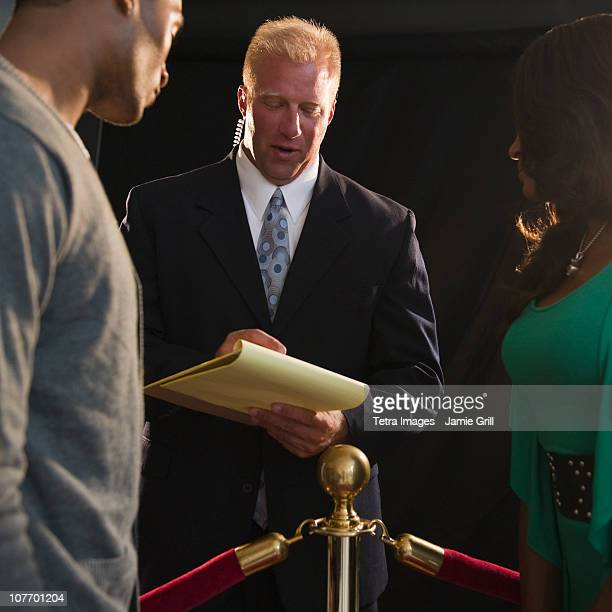 usa, new jersey, jersey city, bouncer checking invitation at red carpet event - doorman stock photos and pictures