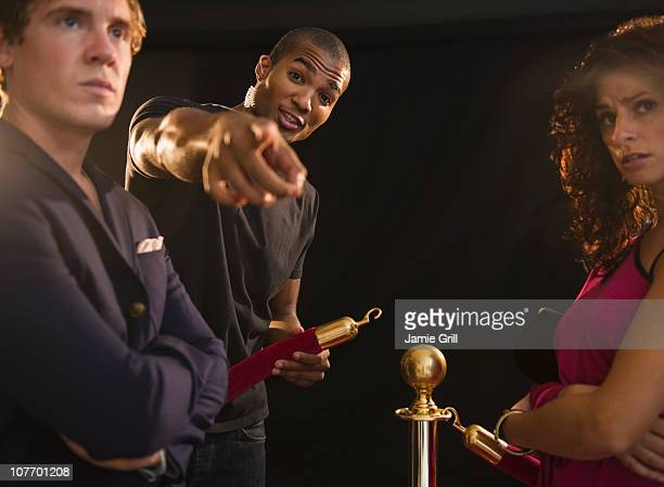 usa, new jersey, jersey city, bouncer pointing outside club - doorman stock photos and pictures