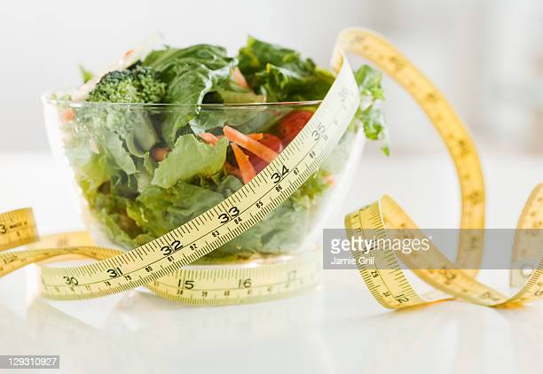 USA, New Jersey, Jersey City, Bowl of salad and tape measure