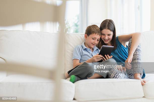 USA, New Jersey, Jersey City, Boy and girl (8-9, 10-11) sitting on sofa using digital tablet